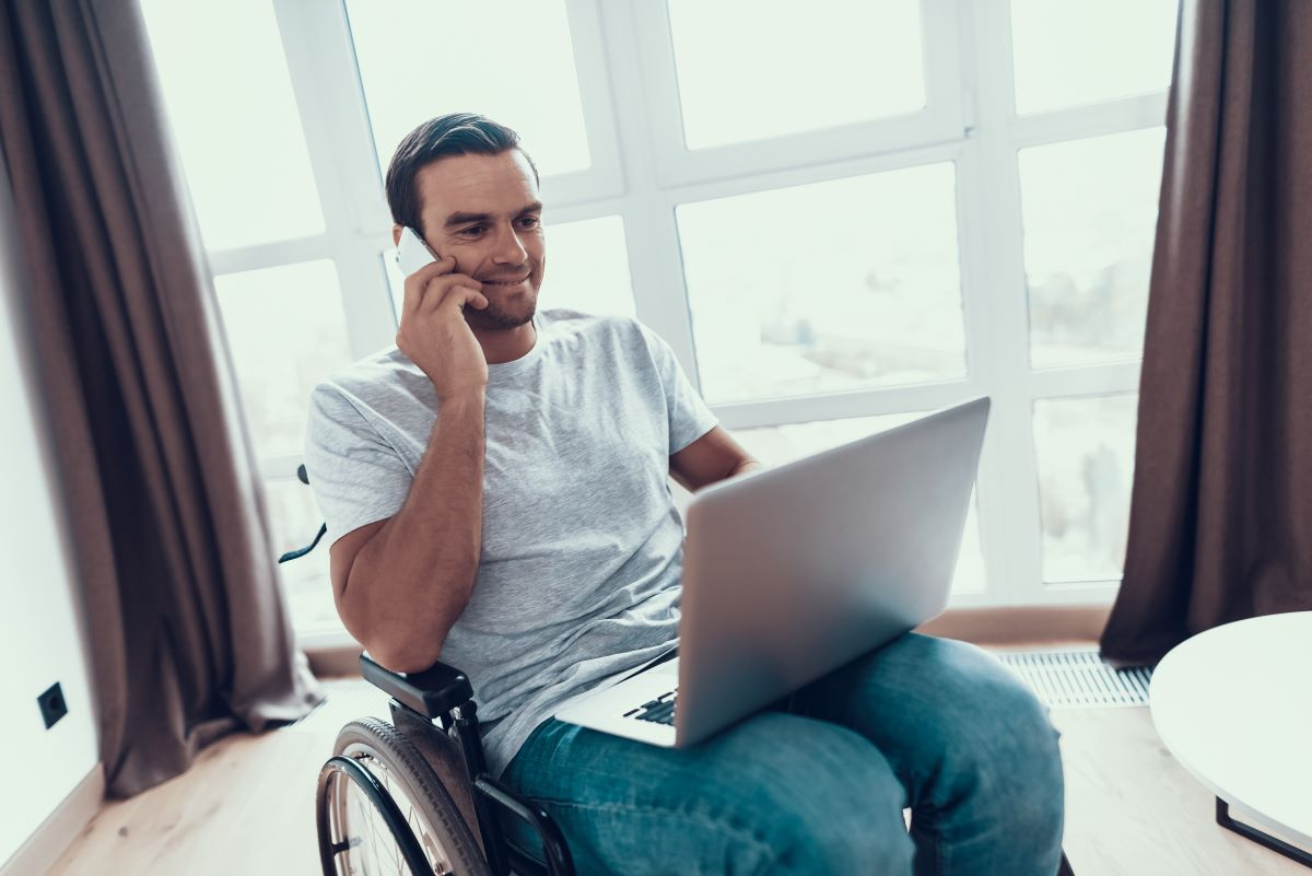 Video Gifts for Veterans and Active Duty Military Members, Reasons to Give a Veteran a Video Tribute, Veteran in Wheelchair Smiles at Computer Screen